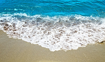 Sunny sand and wave on the sea.