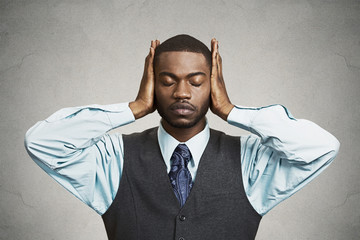Man covers his ears, eyes closed, hear, see no evil concept