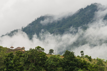 small house on mountain with fog and cloud
