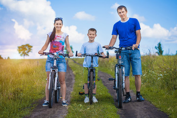 Happy family are riding bicycle in the field