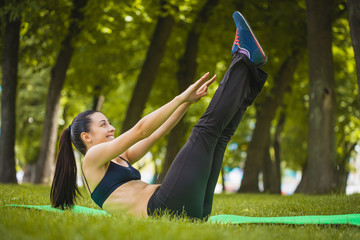 Pretty woman doing exercises in the park