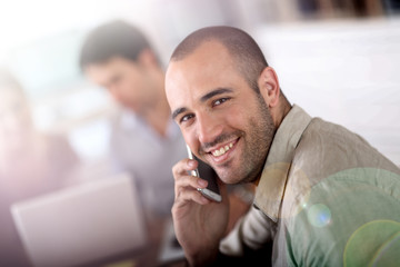 Cheerful salesman talking on the phone