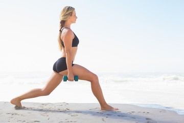 Fit blonde doing weighted lunges on the beach