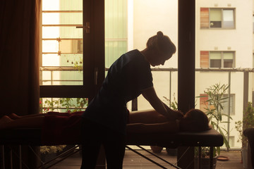 Silhouette of masseuse treating client