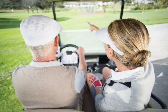 Golfing couple driving in their golf buggy with woman pointing