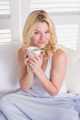 Happy blonde relaxing on the couch with coffee