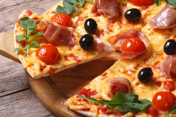 piece of pizza with ham, tomatoes, black olives and arugula