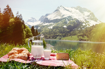 Wall Mural - Milk, cheese and bread served at a picnic on Alpine meadow, Swit