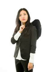 Asian young businesswoman dressed up as black angel looking up