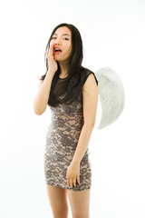 Asian young woman dressed up as an angel whispering isolated on