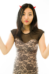 Asian young woman dressed up as a devil with shrugging