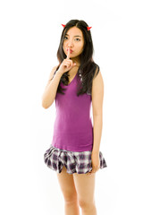 Asian young woman dressed up as a devil with finger on lips