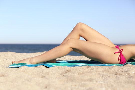 Beauty perfect woman waxing legs sunbathing on the beach