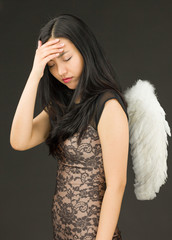 Upset young woman with angel wings pretending with her head in