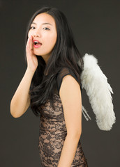 Asian young woman dressed up as an angel whispering