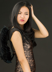 Asian young woman dressed up as a black angel scratching her