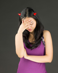 Devil side of a young Asian woman suffering with headache