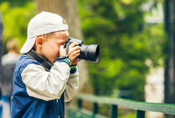 Little boy with photo camera makes a shoot