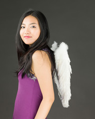 Angel side of a young Asian woman standing and smiling