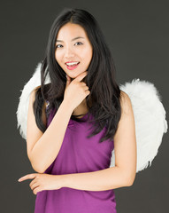 Angel side of a young Asian woman standing with hand on chin and