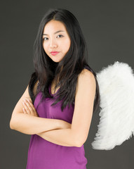 Angel side of a young Asian woman standing with her arms crossed