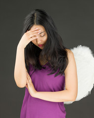 Angel side of a young Asian woman suffering with headache and