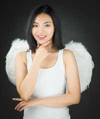 Asian young woman dressed up as an angel with hand on chin and