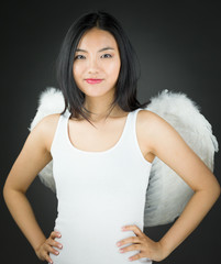 Confident Asian young woman dressed up as an angel with her arms