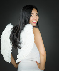 Rear view of a smiling Asian young woman dressed up as an angel