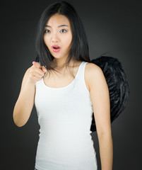 Shocked Asian young woman dressed up as an angel pointing