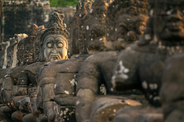Stone carved statues of Asuras on the bridge to Angkor Thom in A