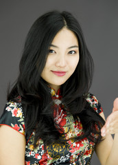 Asian young woman giving hand for handshake isolated on colored