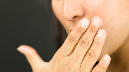 Extreme close-up of a young woman covering her mouth with her