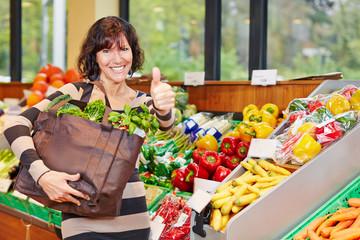 Frau im Biomarkt hält Daumen hoch