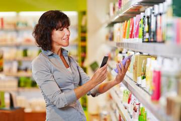 Frau mit Smartphone scannt Produkt im Supermarkt
