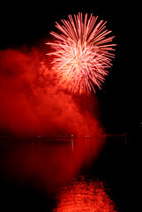 Red firework reflected in water