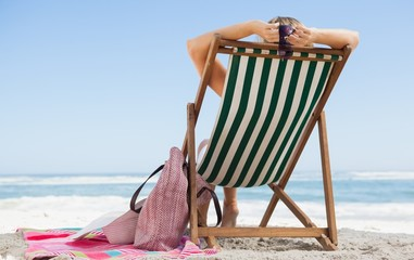 Woman sitting in deck chair at the beach with her beach bag and