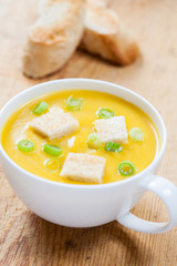 Creamy pumpkin soup with croutons and lightly toasted baguette