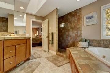 Spacious bathroom with corner bath tub and open shower