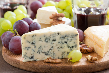 Assorted snacks and red wine, blue cheese, cheddar, camembert