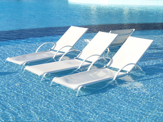 Three chaise longue at the poolside