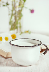 Milk in metal mug and chamomile flowers in open book