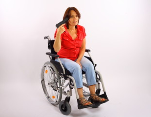 Frau im Rollstuhl mit Pistole