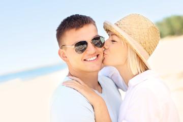 Woman kissing a man at the beach
