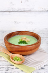 Tasty peas soup on wooden table