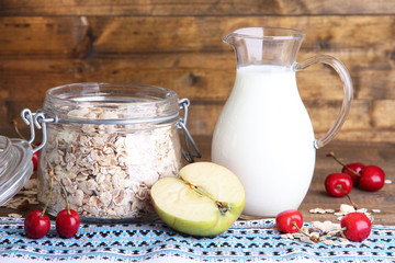 Homemade granola in glass jar, fresh cherries and jug with milk