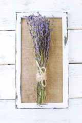 Lavender flowers and wooden frame on wooden background