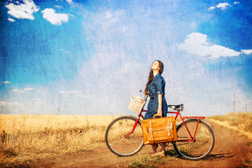 Brunette girl  with bycicle and suitcase on country side road.