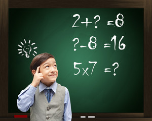 Little boy Thinking mathematics on blackboard in the background