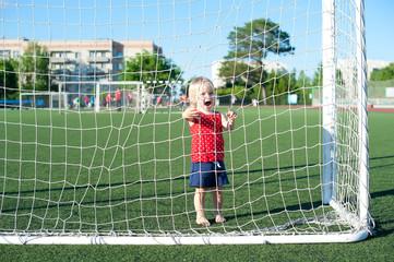 Little girl football fan on the green grass field with ball